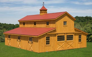 Large two story horse barn with red metal roof and weathervance